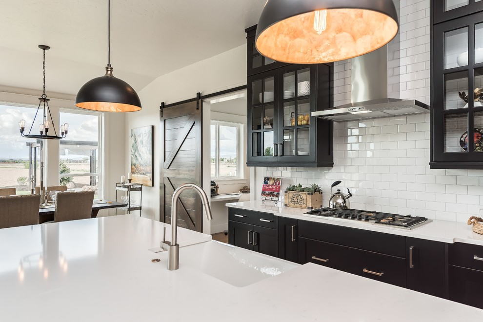 Huge country u-shaped eat-in kitchen photo in Boise with a farmhouse sink, glass-front cabinets, black cabinets, quartz countertops, white backsplash, stainless steel appliances, an island and subway tile backsplash