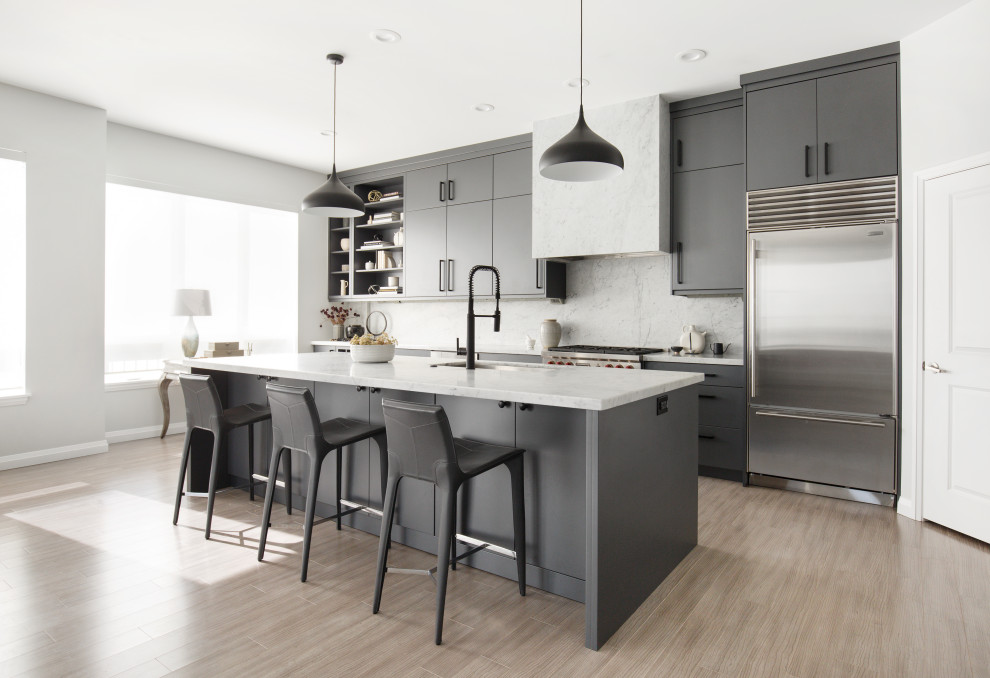 Eat-in kitchen - mid-sized contemporary galley light wood floor and beige floor eat-in kitchen idea in Salt Lake City with an undermount sink, flat-panel cabinets, marble countertops, gray backsplash, marble backsplash, stainless steel appliances, an island, gray countertops and gray cabinets