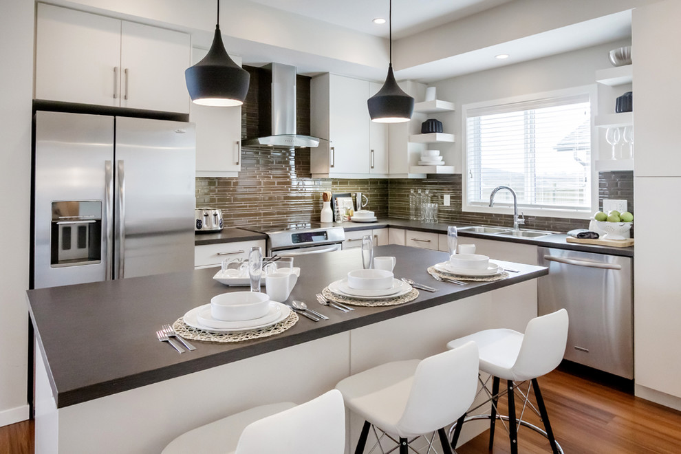 Example of a minimalist l-shaped kitchen design in Calgary with flat-panel cabinets, white cabinets, stainless steel appliances, a drop-in sink and green backsplash