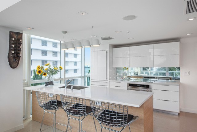 Inspiration for a mid-sized contemporary galley porcelain tile open concept kitchen remodel in Miami with an undermount sink, flat-panel cabinets, white cabinets, quartz countertops, stainless steel appliances and an island
