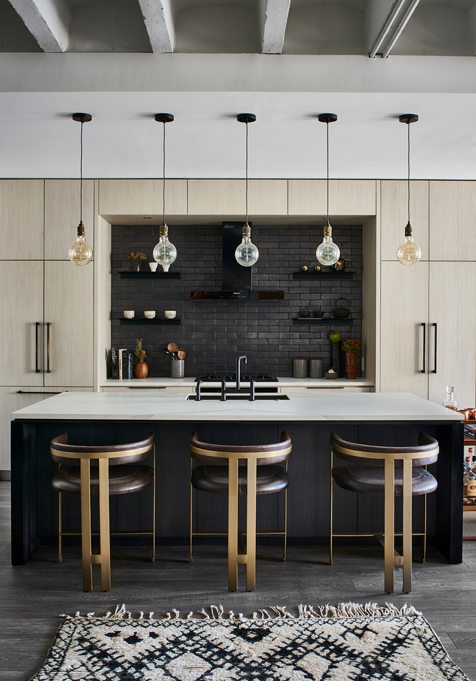 Trendy galley medium tone wood floor and gray floor kitchen photo in Atlanta with an undermount sink, flat-panel cabinets, light wood cabinets, black backsplash, paneled appliances, an island and white countertops