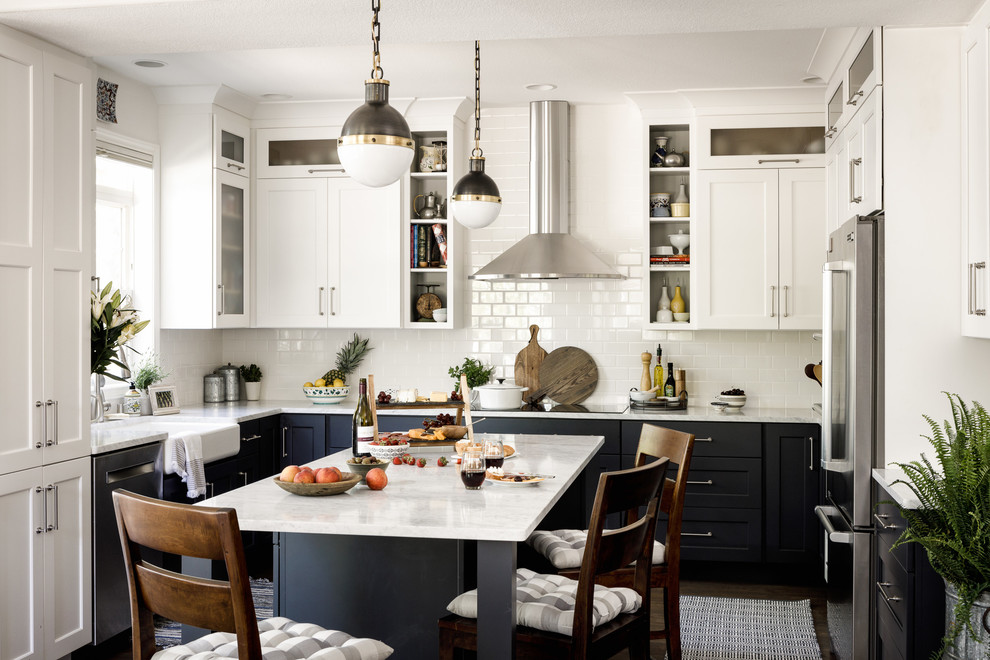 Inspiration for a transitional u-shaped eat-in kitchen remodel in Denver with a farmhouse sink, shaker cabinets, blue cabinets, white backsplash, subway tile backsplash, stainless steel appliances and an island