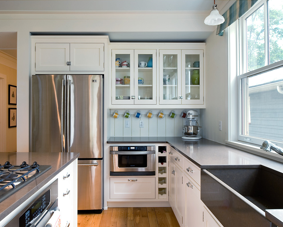 Inspiration for a mid-sized timeless u-shaped light wood floor eat-in kitchen remodel in Detroit with a farmhouse sink, stainless steel appliances, quartz countertops, glass-front cabinets, white cabinets, white backsplash and an island