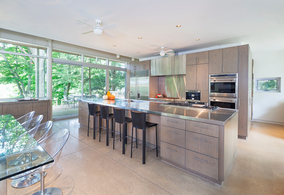 Example of a large trendy galley concrete floor eat-in kitchen design in Grand Rapids with flat-panel cabinets, stainless steel countertops, metallic backsplash, stainless steel appliances, an island and medium tone wood cabinets