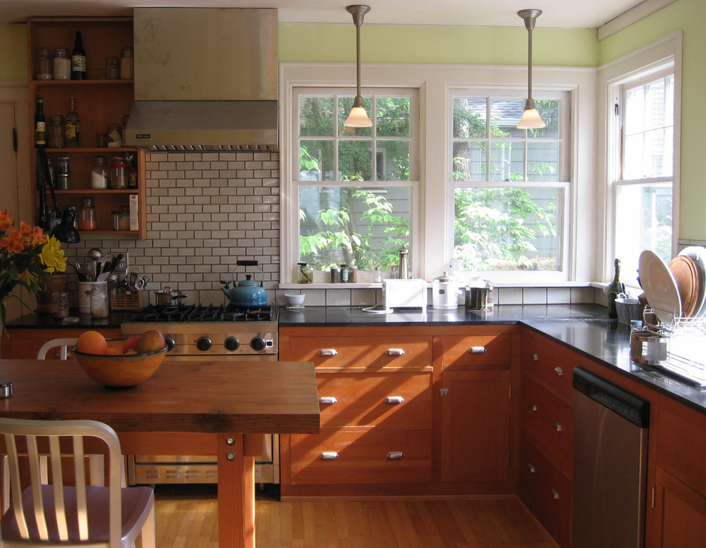 Arts and crafts enclosed kitchen photo in Seattle with stainless steel appliances, granite countertops, medium tone wood cabinets, white backsplash and subway tile backsplash