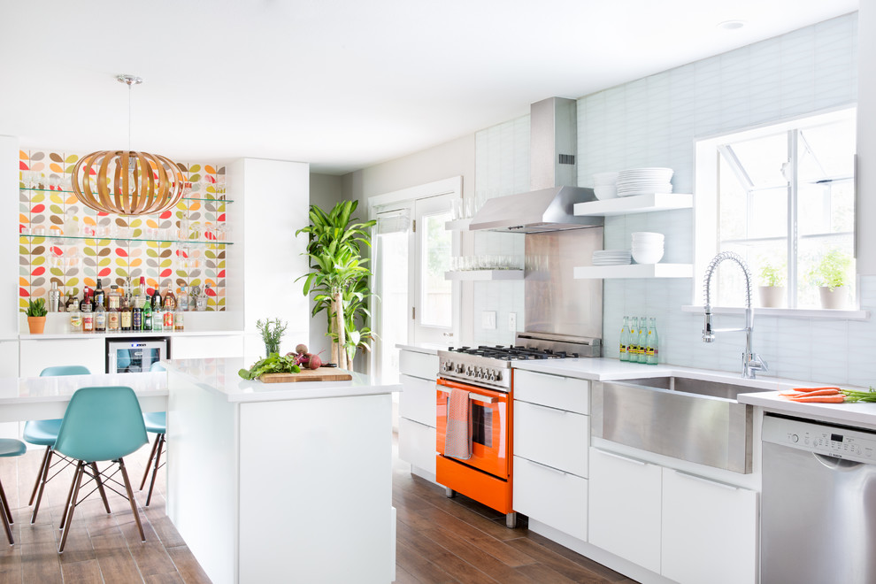 Example of a mid-sized 1950s single-wall ceramic tile eat-in kitchen design in Austin with a farmhouse sink, flat-panel cabinets, white cabinets, quartz countertops, white backsplash, glass tile backsplash, stainless steel appliances and an island