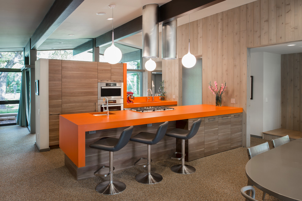 Example of a mid-century modern galley eat-in kitchen design in Austin with an undermount sink, flat-panel cabinets, light wood cabinets, laminate countertops, stainless steel appliances and orange countertops