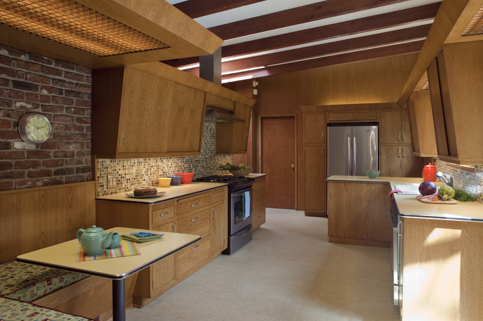 Example of a mid-sized 1960s u-shaped enclosed kitchen design in Portland with stainless steel appliances, flat-panel cabinets, medium tone wood cabinets, laminate countertops, multicolored backsplash and no island