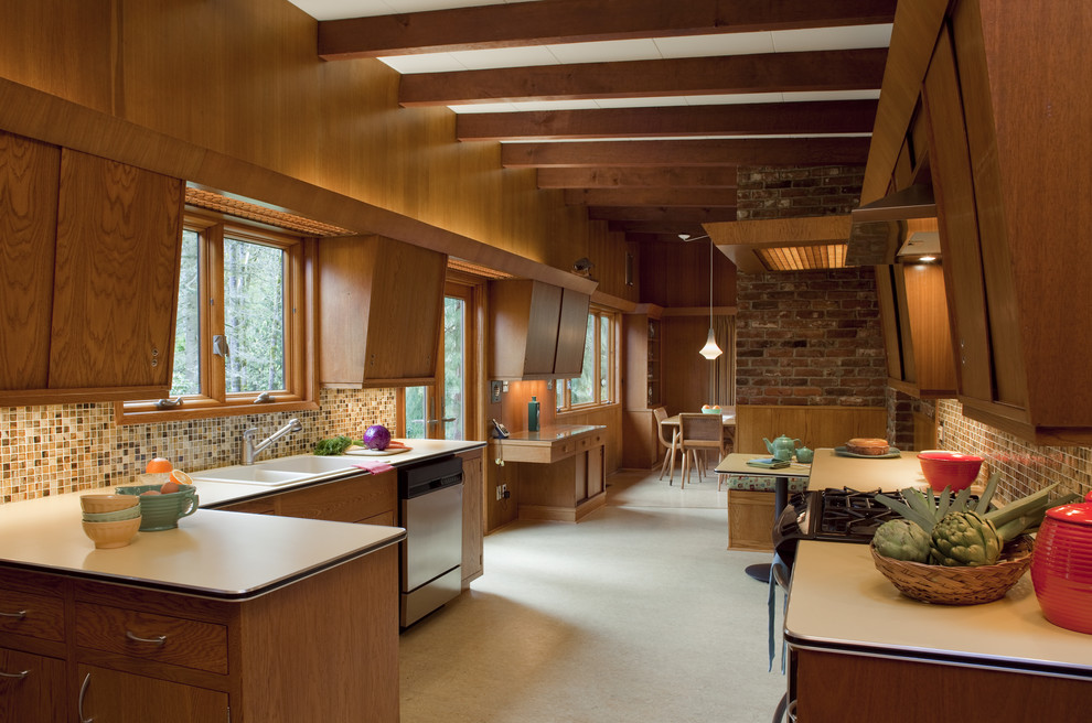 Mid-sized mid-century modern u-shaped carpeted enclosed kitchen photo in Portland with mosaic tile backsplash, a drop-in sink, flat-panel cabinets, medium tone wood cabinets, laminate countertops, multicolored backsplash, stainless steel appliances and no island