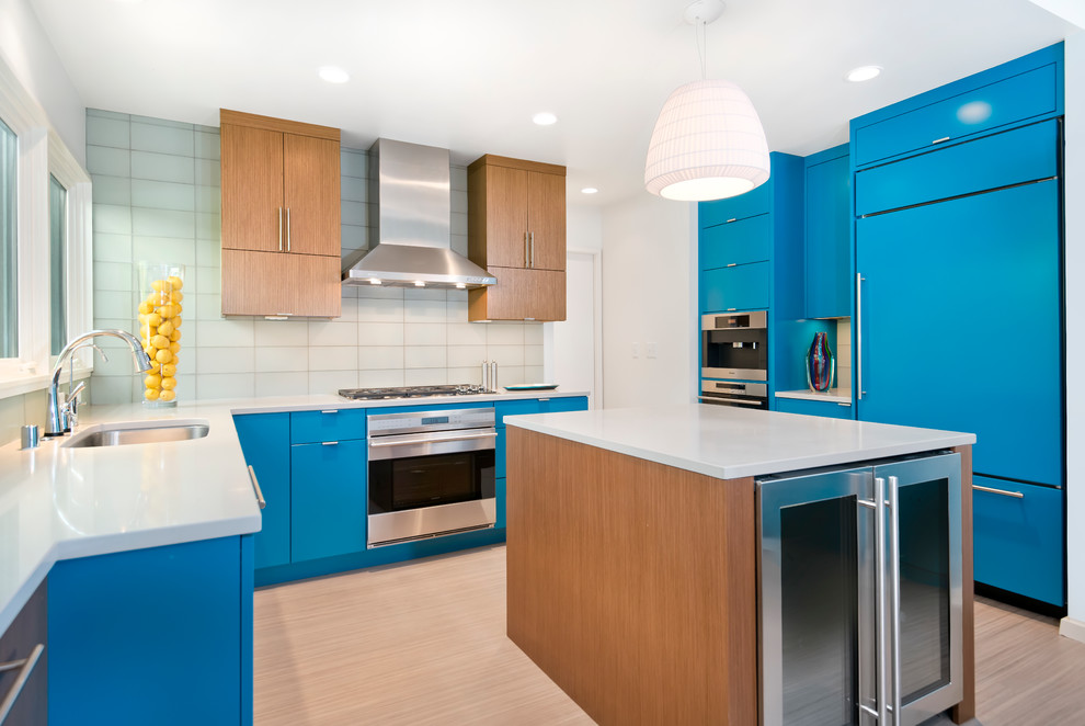 Inspiration for a contemporary u-shaped enclosed kitchen remodel in Milwaukee with an undermount sink, flat-panel cabinets, blue cabinets, quartz countertops, glass tile backsplash and stainless steel appliances