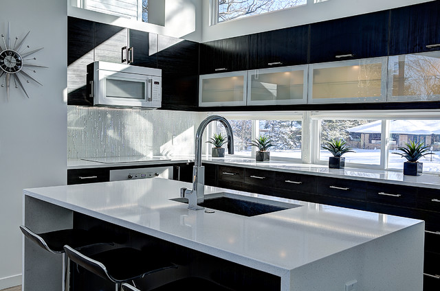 Inspiration for a mid-sized contemporary l-shaped light wood floor open concept kitchen remodel in Grand Rapids with an undermount sink, glass-front cabinets, quartz countertops, white appliances, an island, black cabinets, white backsplash and glass tile backsplash