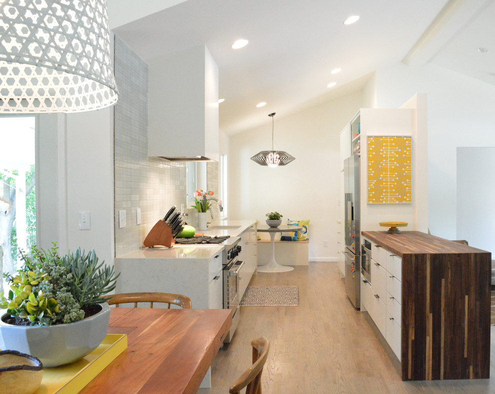 Example of a mid-sized mid-century modern galley dark wood floor and brown floor eat-in kitchen design in Denver with an undermount sink, flat-panel cabinets, white cabinets, solid surface countertops, gray backsplash, mosaic tile backsplash and stainless steel appliances