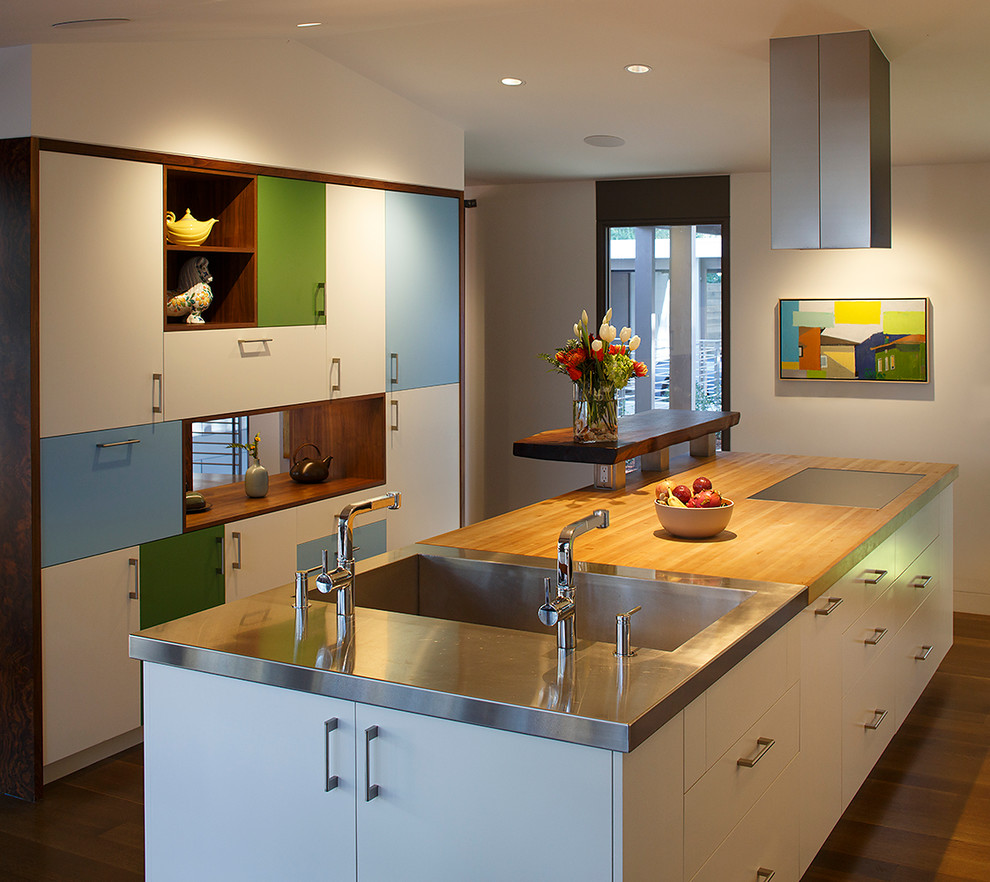 Eat-in kitchen - large 1960s galley medium tone wood floor eat-in kitchen idea in San Francisco with an integrated sink, flat-panel cabinets, white cabinets, wood countertops, white backsplash, glass sheet backsplash, stainless steel appliances and an island