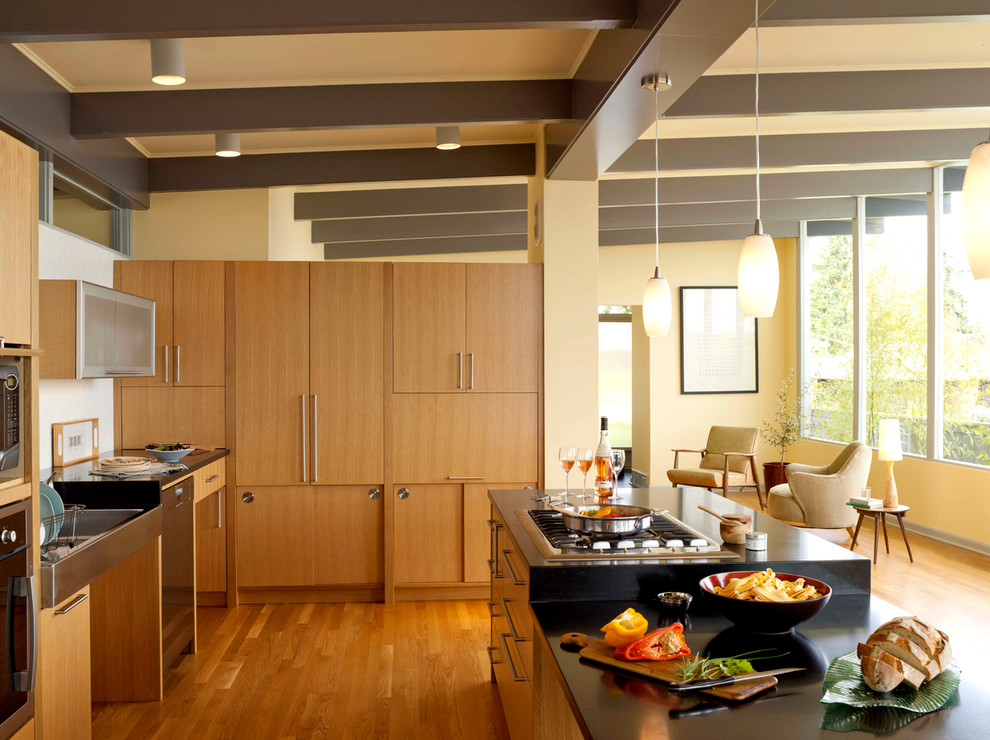 Large mid-century modern l-shaped medium tone wood floor kitchen photo in Seattle with flat-panel cabinets, medium tone wood cabinets, a farmhouse sink, soapstone countertops, stainless steel appliances, an island and black countertops