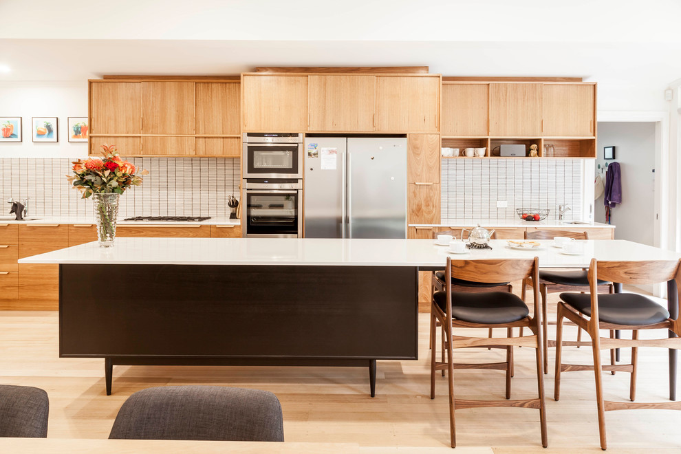 Open concept kitchen - large 1960s galley light wood floor and beige floor open concept kitchen idea in Melbourne with an island, quartz countertops, an undermount sink, beige backsplash, ceramic backsplash, stainless steel appliances, flat-panel cabinets and light wood cabinets