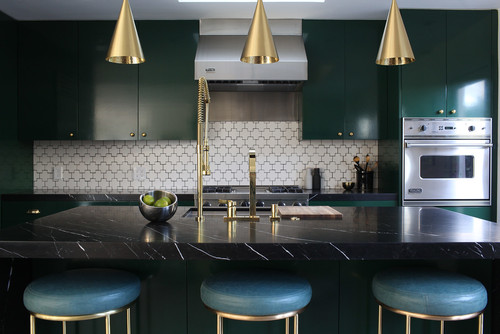 Modern dark kitchen with green cabinets, blue seat cushions on stools, and gold pendant lighting fixtures and metal finish