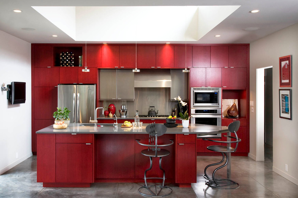 Example of a trendy galley enclosed kitchen design in Albuquerque with an undermount sink, flat-panel cabinets, red cabinets, metallic backsplash and stainless steel appliances