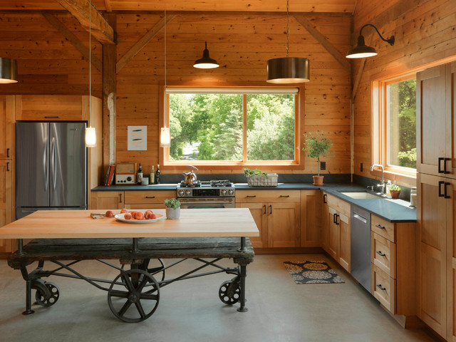 Inspiration for a mid-sized country l-shaped concrete floor and gray floor kitchen remodel in Burlington with an undermount sink, shaker cabinets, medium tone wood cabinets, stainless steel appliances, an island, wood countertops, wood backsplash and black countertops