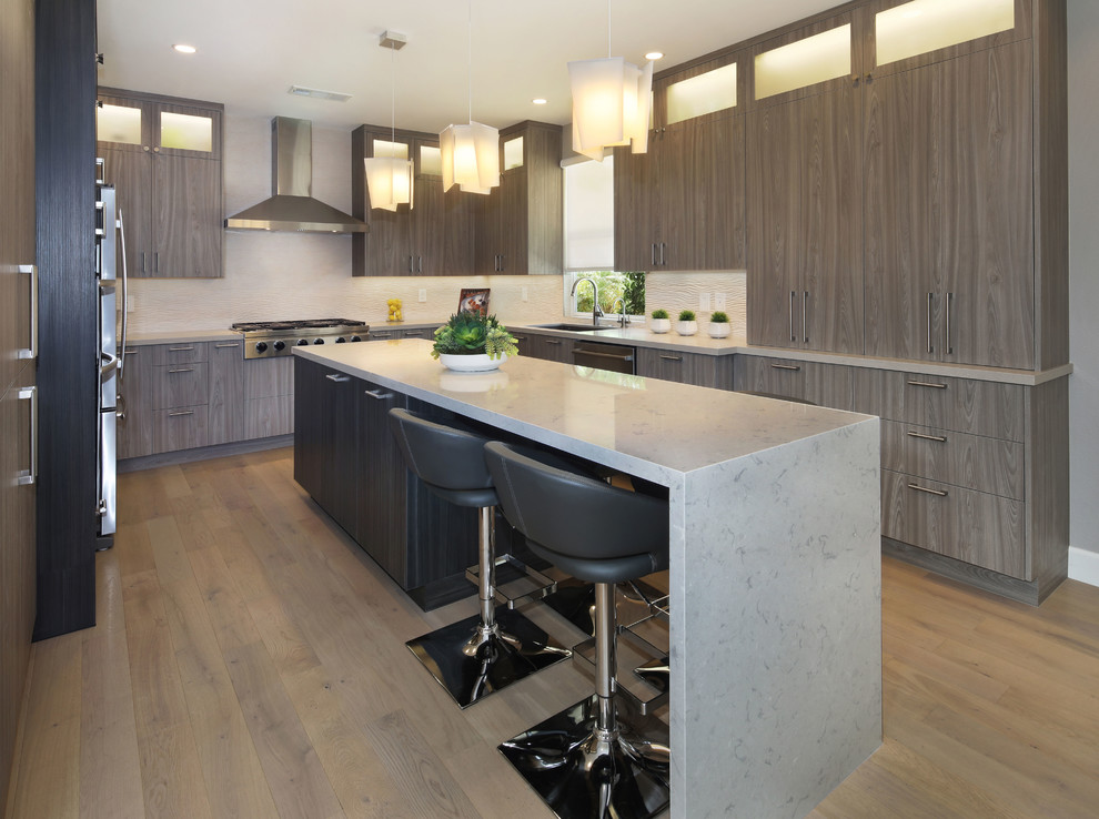 Example of a mid-sized trendy u-shaped light wood floor and beige floor eat-in kitchen design in Orange County with an undermount sink, flat-panel cabinets, quartz countertops, beige backsplash, porcelain backsplash, stainless steel appliances, an island, white countertops and medium tone wood cabinets