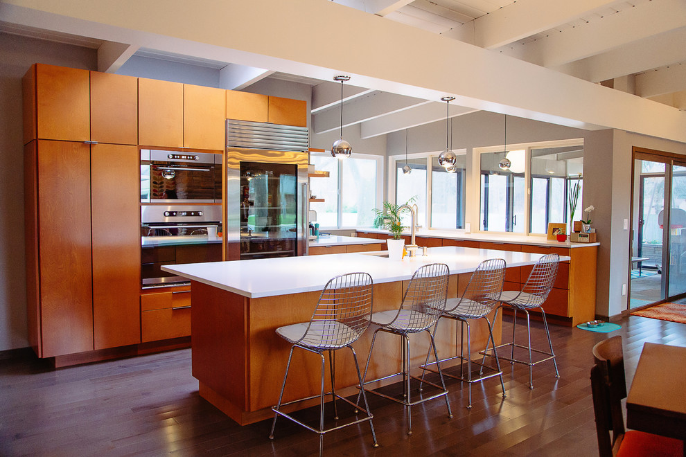 Inspiration for a mid-sized 1960s medium tone wood floor open concept kitchen remodel in Grand Rapids with an undermount sink, flat-panel cabinets, medium tone wood cabinets, stainless steel appliances and an island