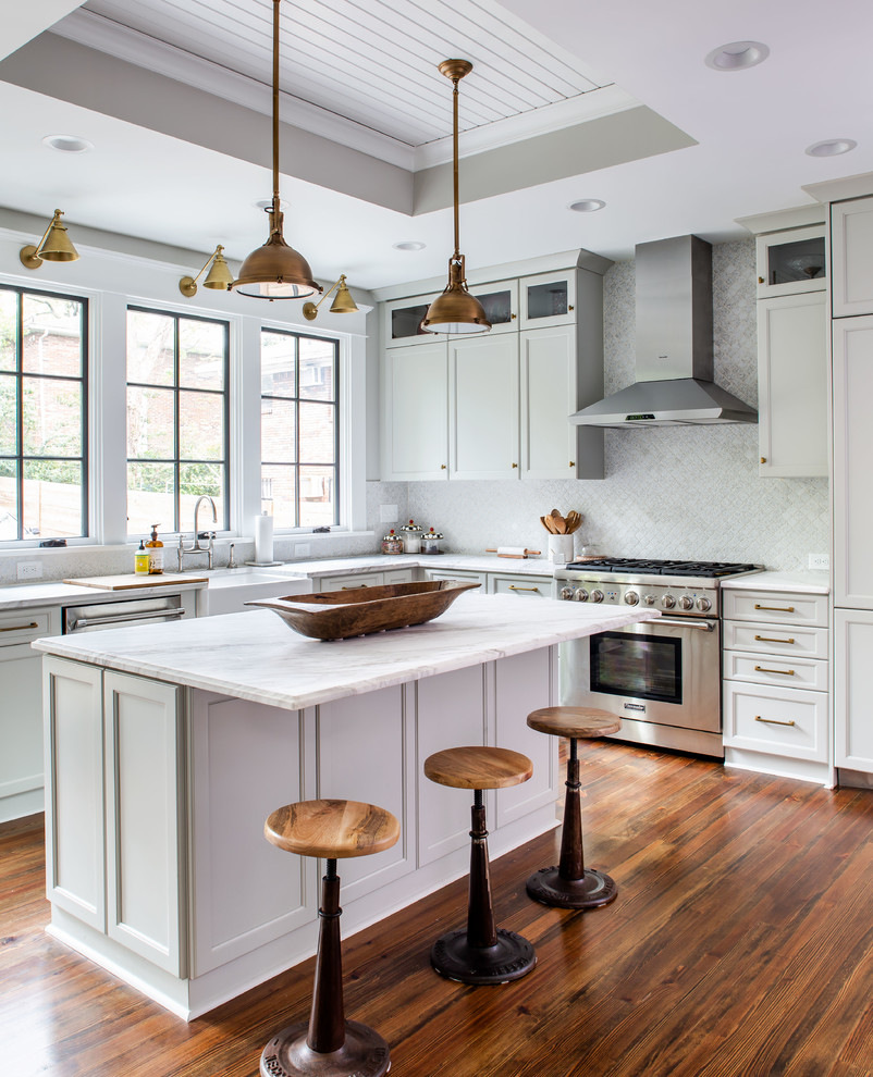 Kitchen - transitional l-shaped dark wood floor and brown floor kitchen idea in Atlanta with a farmhouse sink, recessed-panel cabinets, white cabinets, white backsplash, stainless steel appliances, an island and white countertops