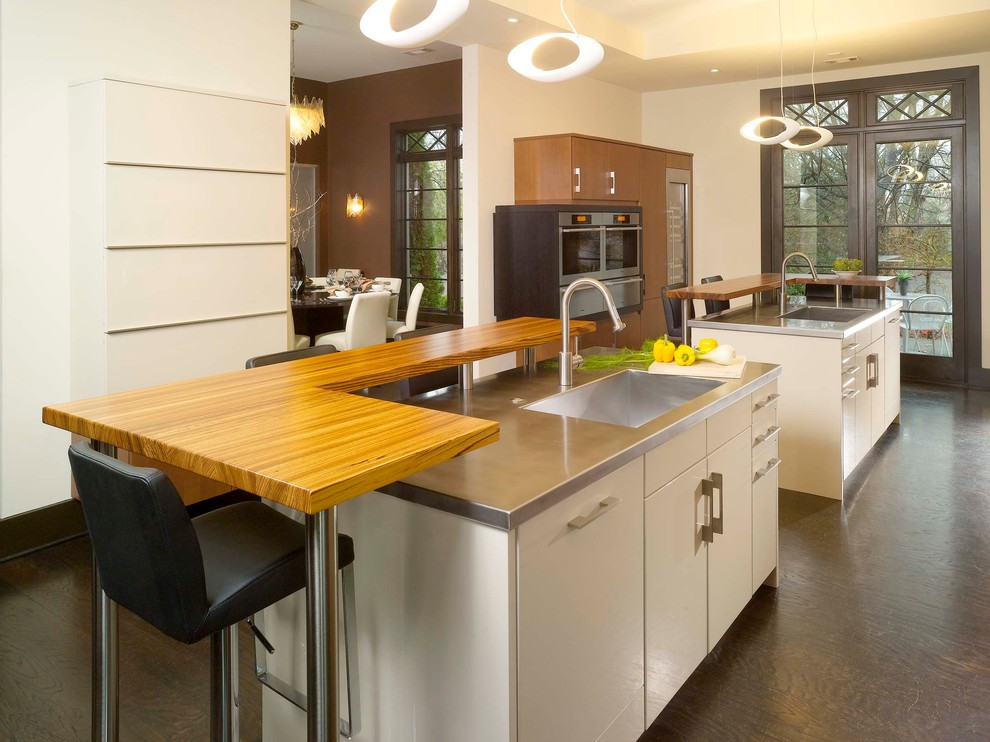 Example of a minimalist enclosed kitchen design in Atlanta with stainless steel countertops, an integrated sink, flat-panel cabinets, stainless steel appliances and beige cabinets