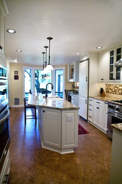 Eat-in kitchen - large traditional l-shaped concrete floor eat-in kitchen idea in Seattle with a farmhouse sink, raised-panel cabinets, white cabinets, granite countertops, multicolored backsplash, mosaic tile backsplash, paneled appliances and an island
