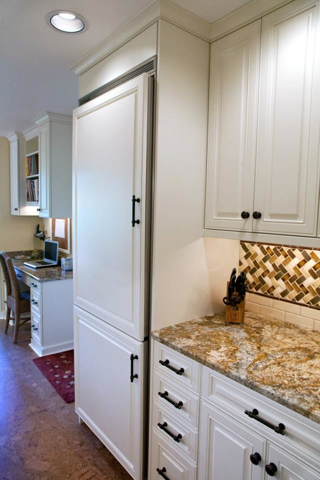 Large elegant l-shaped concrete floor eat-in kitchen photo in Seattle with a farmhouse sink, raised-panel cabinets, white cabinets, granite countertops, multicolored backsplash, mosaic tile backsplash, paneled appliances and an island