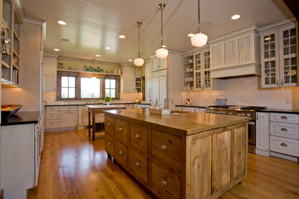Example of a cottage kitchen design in Minneapolis with glass-front cabinets and wood countertops