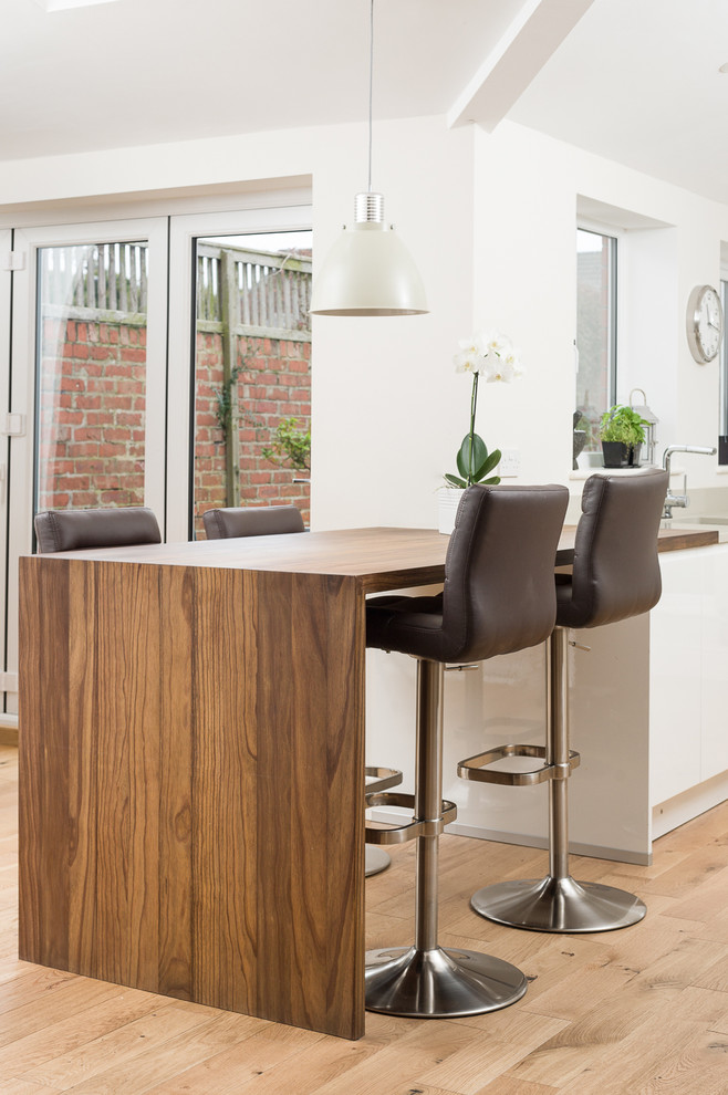Example of a trendy kitchen design in Other with flat-panel cabinets, white cabinets, wood countertops and a peninsula
