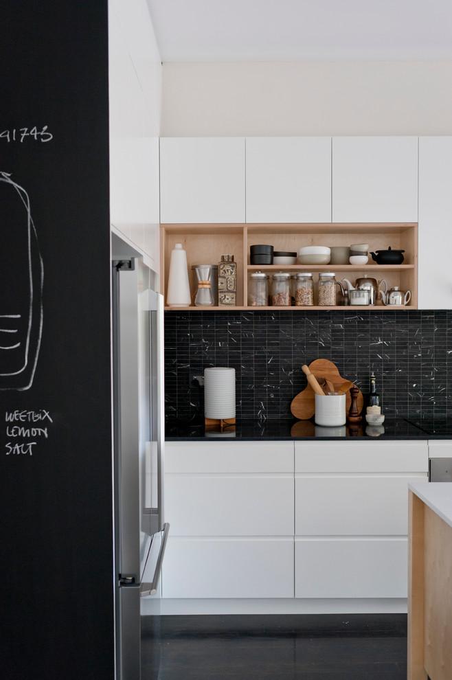 Danish black floor kitchen photo in Sydney with flat-panel cabinets and black backsplash