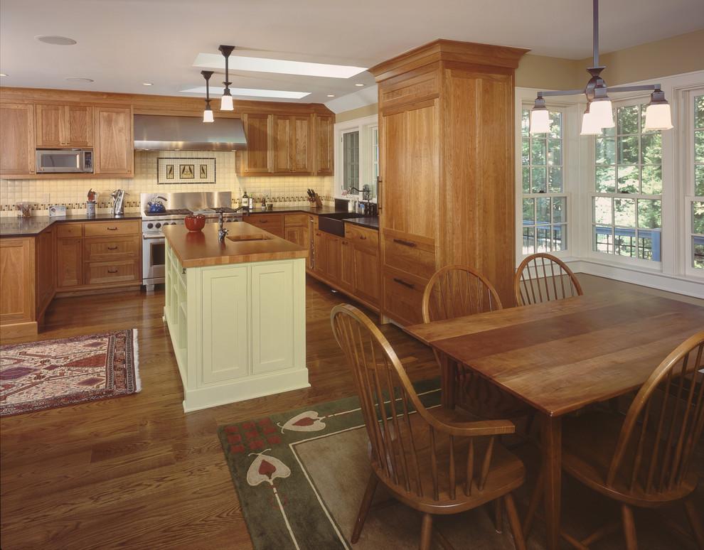 Example of a mid-sized mountain style u-shaped medium tone wood floor eat-in kitchen design in New York with wood countertops, medium tone wood cabinets, a farmhouse sink, shaker cabinets, white backsplash, porcelain backsplash, paneled appliances and an island