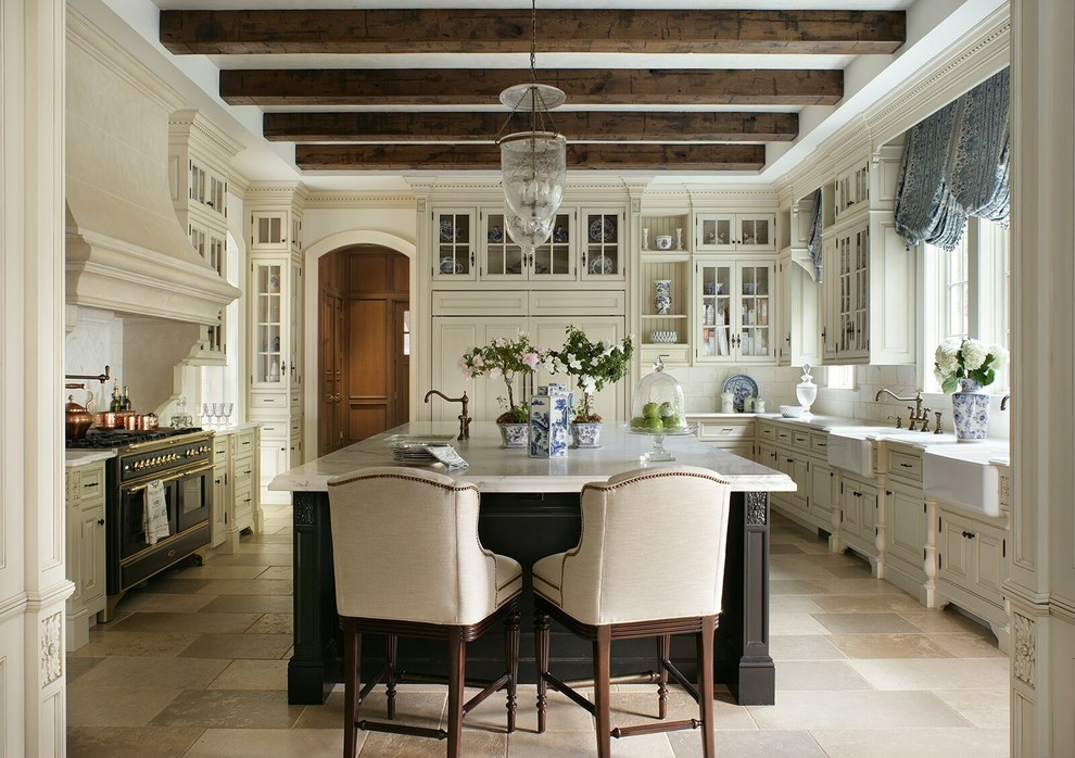 Example of a classic u-shaped beige floor enclosed kitchen design in New York with a farmhouse sink, raised-panel cabinets, beige cabinets, white backsplash, black appliances and an island