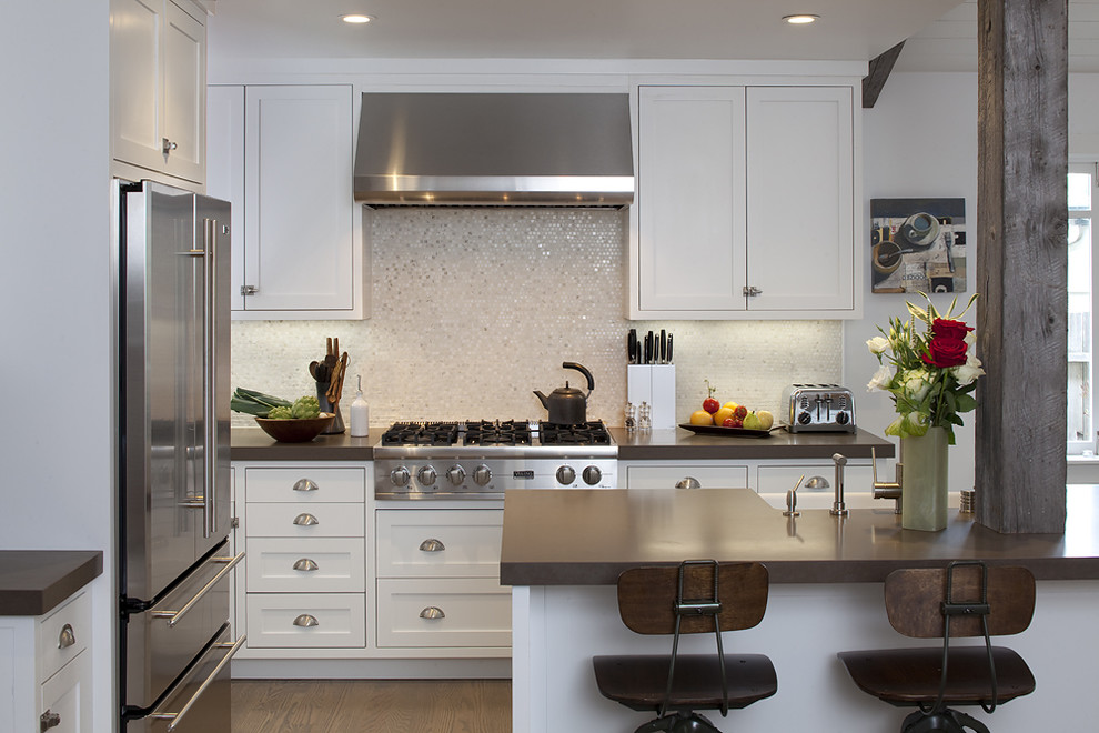 Example of a classic kitchen design in San Francisco with stainless steel appliances, a farmhouse sink, shaker cabinets, white cabinets, mosaic tile backsplash and metallic backsplash