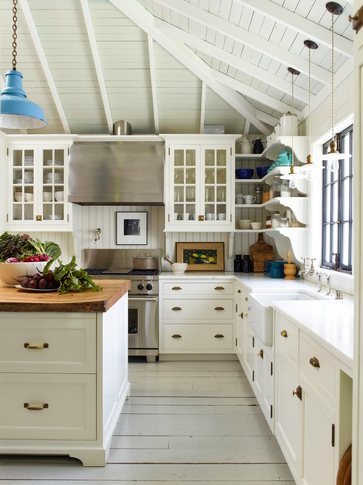 Large cottage l-shaped painted wood floor kitchen photo in San Francisco with a farmhouse sink, recessed-panel cabinets, white cabinets, wood countertops, white backsplash, stainless steel appliances and an island