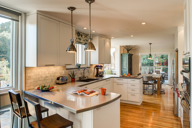 Mid-sized transitional u-shaped medium tone wood floor eat-in kitchen photo in San Francisco with an undermount sink, flat-panel cabinets, white cabinets, quartz countertops, gray backsplash, ceramic backsplash, stainless steel appliances and a peninsula