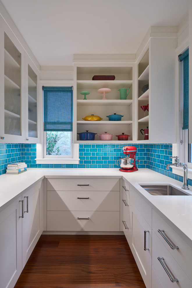 Inspiration for a mid-sized contemporary u-shaped medium tone wood floor and brown floor kitchen pantry remodel in San Francisco with an undermount sink, open cabinets, white cabinets, blue backsplash, subway tile backsplash, white countertops and solid surface countertops