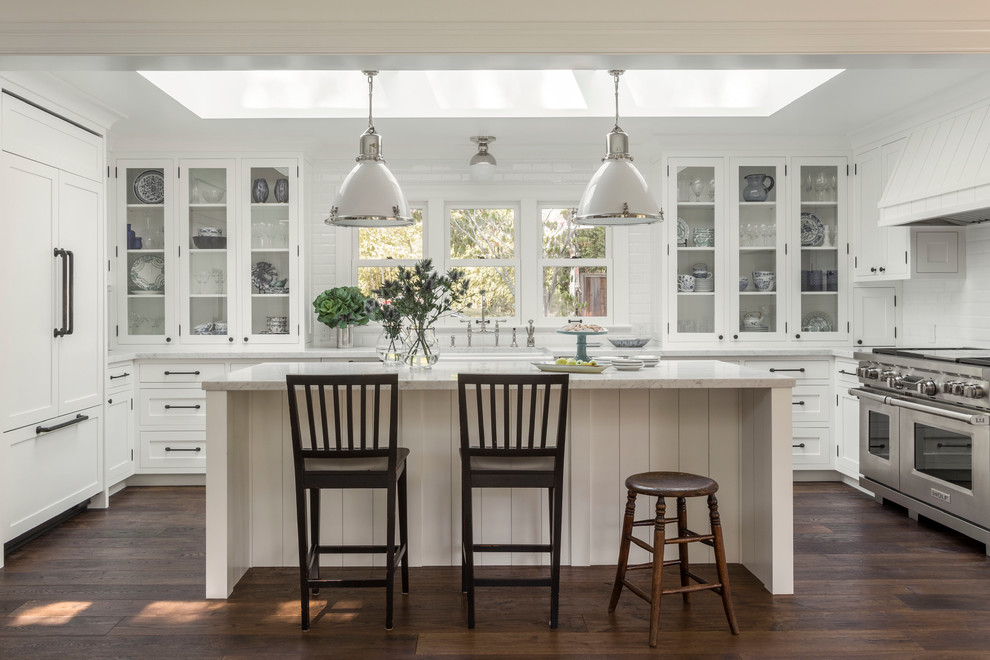 Large country u-shaped dark wood floor open concept kitchen photo in San Francisco with a farmhouse sink, white cabinets, white backsplash, subway tile backsplash, stainless steel appliances, an island and glass-front cabinets