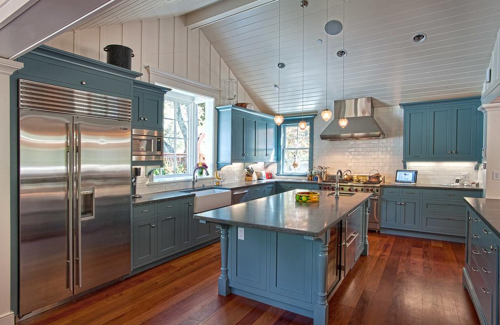Elegant u-shaped dark wood floor kitchen photo in San Francisco with a farmhouse sink, shaker cabinets, blue cabinets, white backsplash, subway tile backsplash, stainless steel appliances and an island