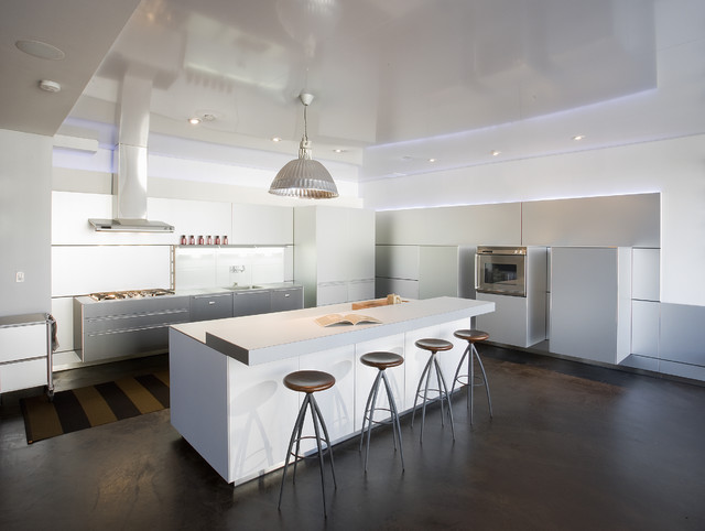 Example of a trendy kitchen design in Seattle with flat-panel cabinets, white cabinets, laminate countertops and paneled appliances