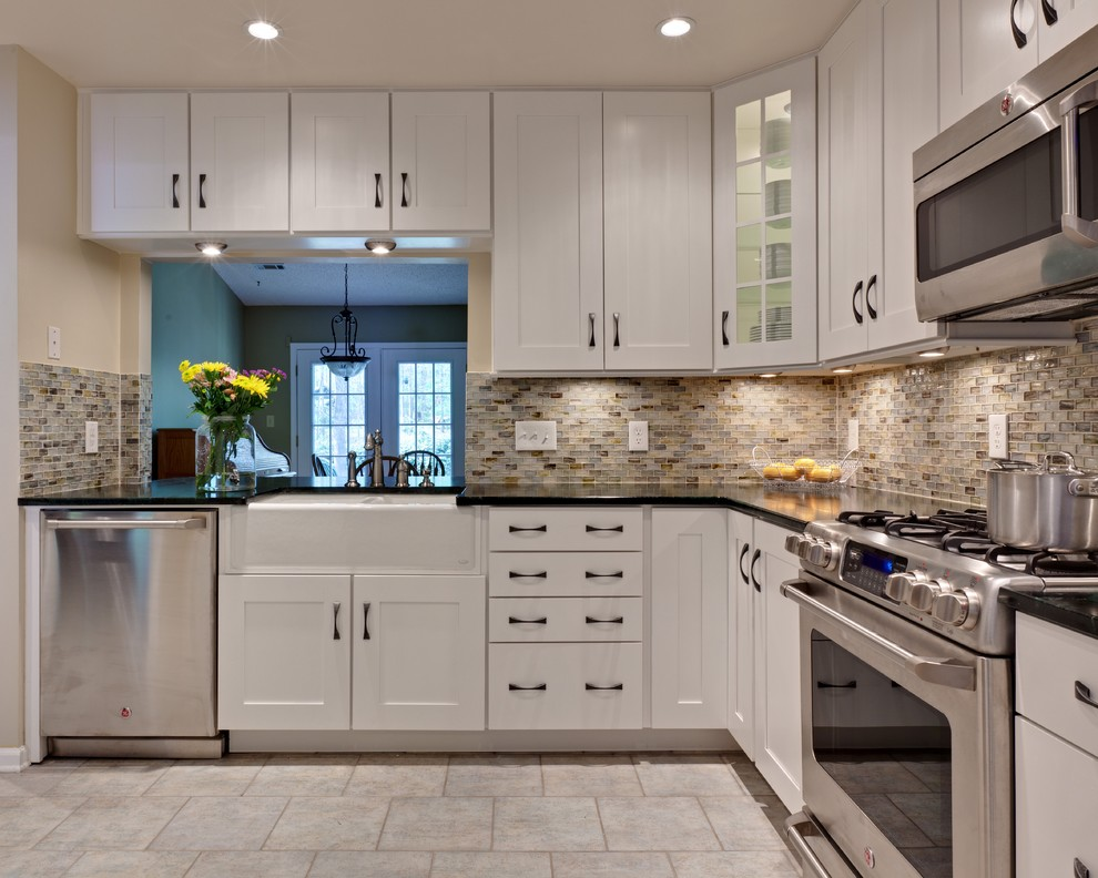 Inspiration for a small timeless u-shaped porcelain tile and beige floor eat-in kitchen remodel in Atlanta with a farmhouse sink, white cabinets, recessed-panel cabinets, soapstone countertops, multicolored backsplash, glass tile backsplash, stainless steel appliances, an island and green countertops