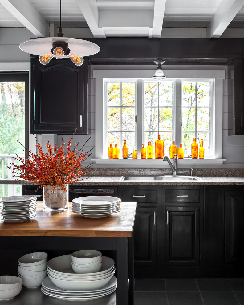 Example of a cottage single-wall black floor kitchen design in New York with a drop-in sink, raised-panel cabinets, black cabinets, gray backsplash and an island