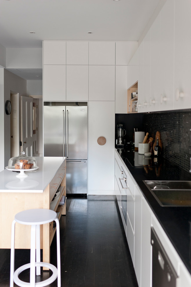 Scandinavian kitchen in Sydney with a drop-in sink, black splashback, mosaic tile splashback, stainless steel appliances, white cabinets, flat-panel cabinets and black floor.