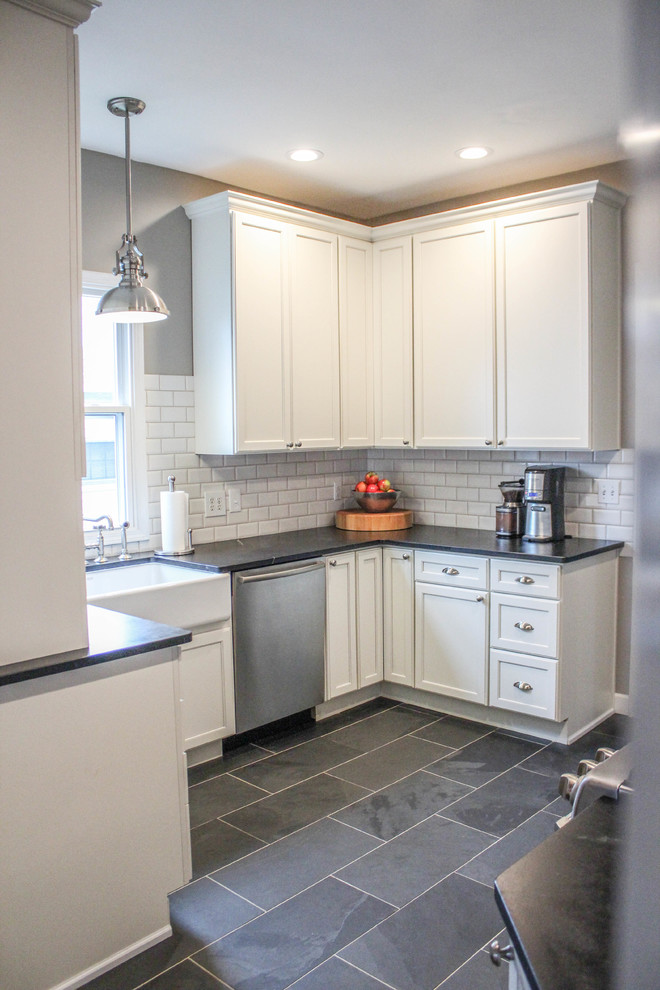 Country u-shaped gray floor eat-in kitchen photo in Cincinnati with a farmhouse sink, recessed-panel cabinets, white cabinets, soapstone countertops, white backsplash, subway tile backsplash and stainless steel appliances
