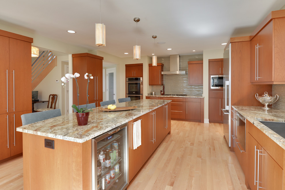 Example of a large trendy u-shaped light wood floor and brown floor eat-in kitchen design in Milwaukee with an undermount sink, flat-panel cabinets, medium tone wood cabinets, beige backsplash, matchstick tile backsplash, stainless steel appliances, an island and multicolored countertops