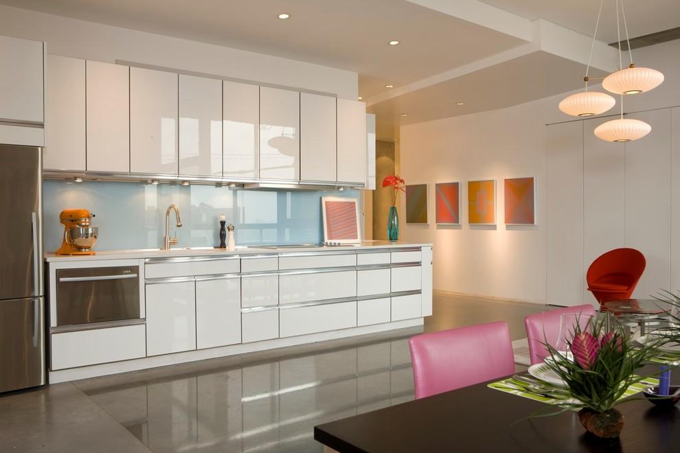 Minimalist single-wall kitchen photo in Kansas City with stainless steel appliances, flat-panel cabinets, white cabinets, blue backsplash and glass sheet backsplash