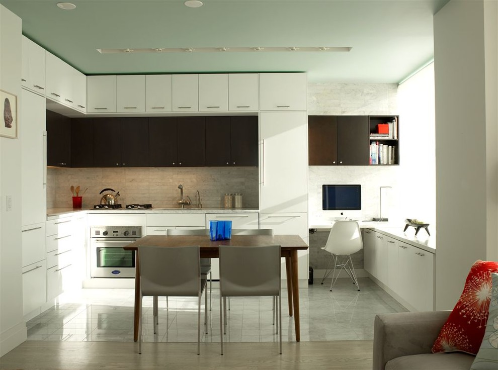 Example of a minimalist l-shaped open concept kitchen design in New York with stainless steel appliances, flat-panel cabinets, white cabinets, white backsplash and stone tile backsplash