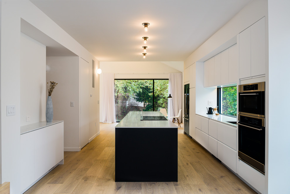 Mid-sized danish galley light wood floor and beige floor open concept kitchen photo in Philadelphia with an undermount sink, flat-panel cabinets, white cabinets, solid surface countertops, window backsplash, black appliances, an island and white countertops