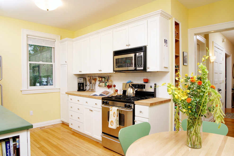 Small elegant galley light wood floor enclosed kitchen photo in Minneapolis with flat-panel cabinets, white cabinets, wood countertops, white backsplash, ceramic backsplash, stainless steel appliances and no island