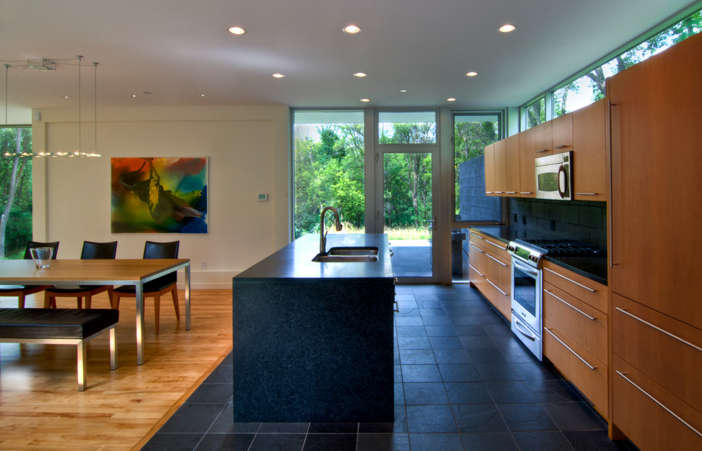 Example of a minimalist galley black floor eat-in kitchen design in Minneapolis with a double-bowl sink, flat-panel cabinets, medium tone wood cabinets, black backsplash and paneled appliances